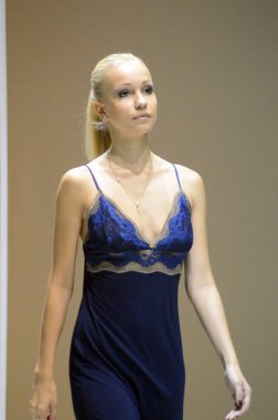 During the Show Lingrie Expo Moscow Autumn 5th International Exhibition of underwear, beachwear, home wear and hosiery Young blonde woman in dark blue negligee Close up