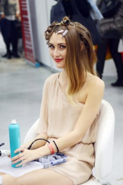 Intercharm XXI International Perfumery and Cosmetics Exhibition Young beautiful brunette girl with a new fashionable hairstyle. The curlers During the show