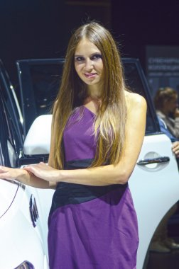 Women in violent dress from Infiniti team near car White Color Moscow International Automobile Salon Look