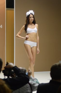 Moscow Traffic 5th International Exhibition of underwear, beachwear, home wear and hosiery Lingrie Expo Young beautiful brunette woman in a white bathing suit White roses