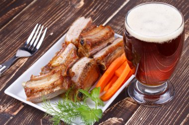 Grilled pork ribs and glass of beer on wooden background