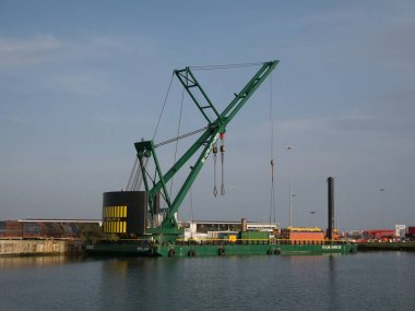 The 250 tonne crane Skylift 2 operating on the submersible Skyline Barge 26 while lifting equipment at docks in Alfred Dock, Birkenhead on the River Mersey in the UK.