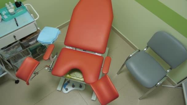 clean orangefarbener gynäkologischer Untersuchungsstuhl mit Bedienfeld. Nahaufnahme, Draufsicht