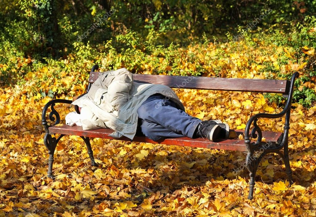 Homeless man is sleeping on a park bench
