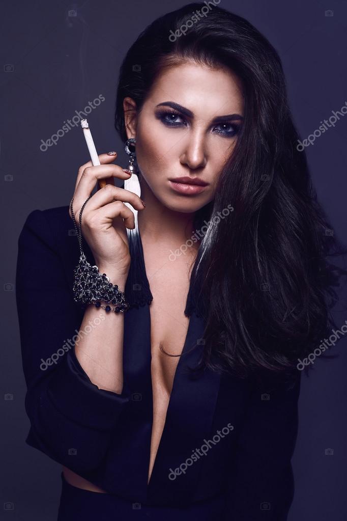 Elegante heiße Brünette Frau raucht eine Zigarette