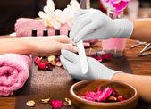 Nahaufnahme Fingernagelpflege durch Maniküre-Spezialist im Schönheitssalon.