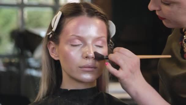 Make-up umělec aplikuje kosmetiku na tvář mladé ženy v salonu krásy