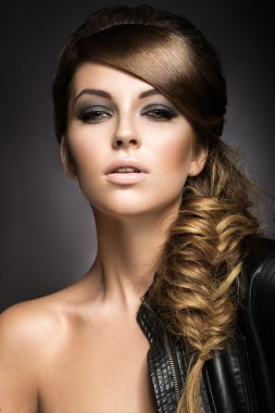 Beautiful girl with bright make-up, perfect skin and hairstyle as a braid.