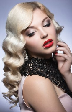 Beautiful blonde in a Hollywood manner with curls, red lips and lace dress. Beauty face.