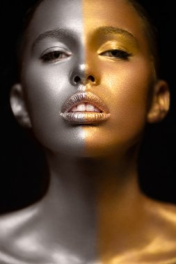 Girl with gold and silver skin in the image of an Oscar. Art image beauty face.