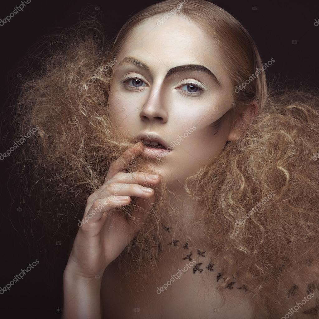 пышная голая женщина с длинными волосами лежит на сером фоне