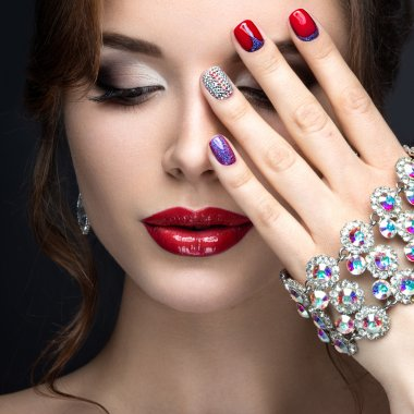 Beautiful girl with a bright evening make-up and red manicure with rhinestones. Nail design. Beauty face.