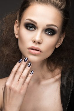 Beautiful girl in leather jacket with bright makeup and manicure