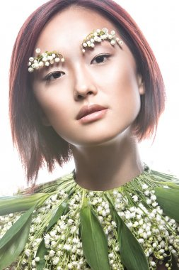Fashion beautiful girl oriental type with delicate natural make-up and flowers. Beauty face.