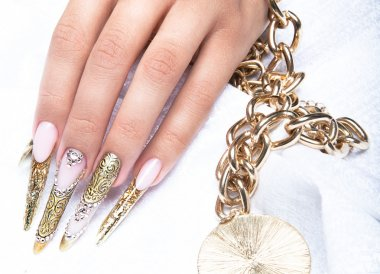 Beautiful long nails in a gold design with rhinestones. Nail art.