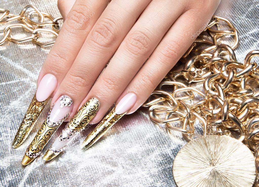 Beautiful long nails in a gold design with rhinestones. Nail art ...