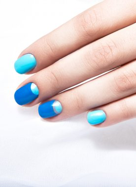 Blue manicure in light and dark colors of lacquer on a white background.