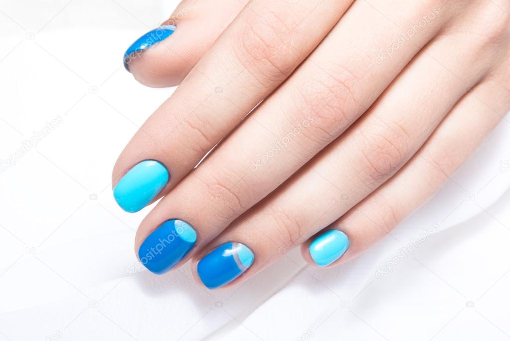 Blue Manicure In Light And Dark Colors Of Lacquer On A White