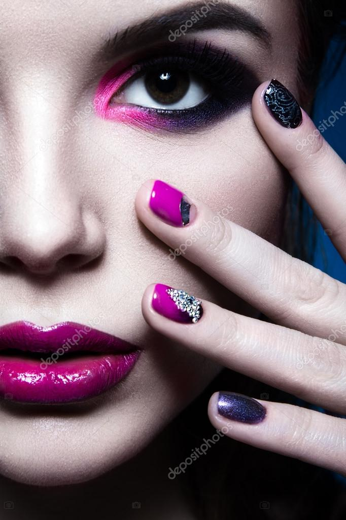 Beautiful girl with bright creative fashion makeup and colorful nail ...