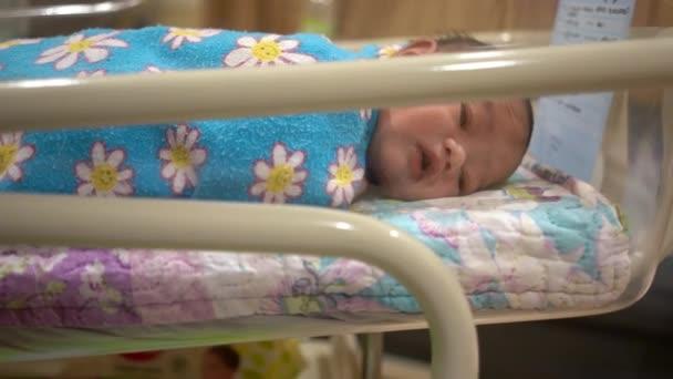 Roztomilý novorozenec chlapec uvnitř postýlky v nemocnici