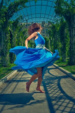 Beautiful woman dancing barefoot in a long blue dress