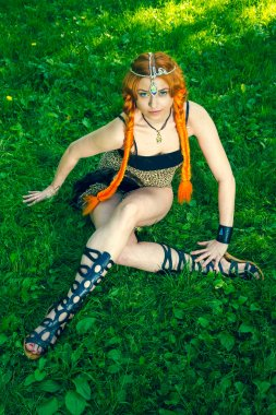 Red head amazon lies on a meadow