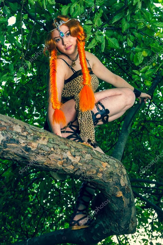 Beautiful red head woman sitting on a tree