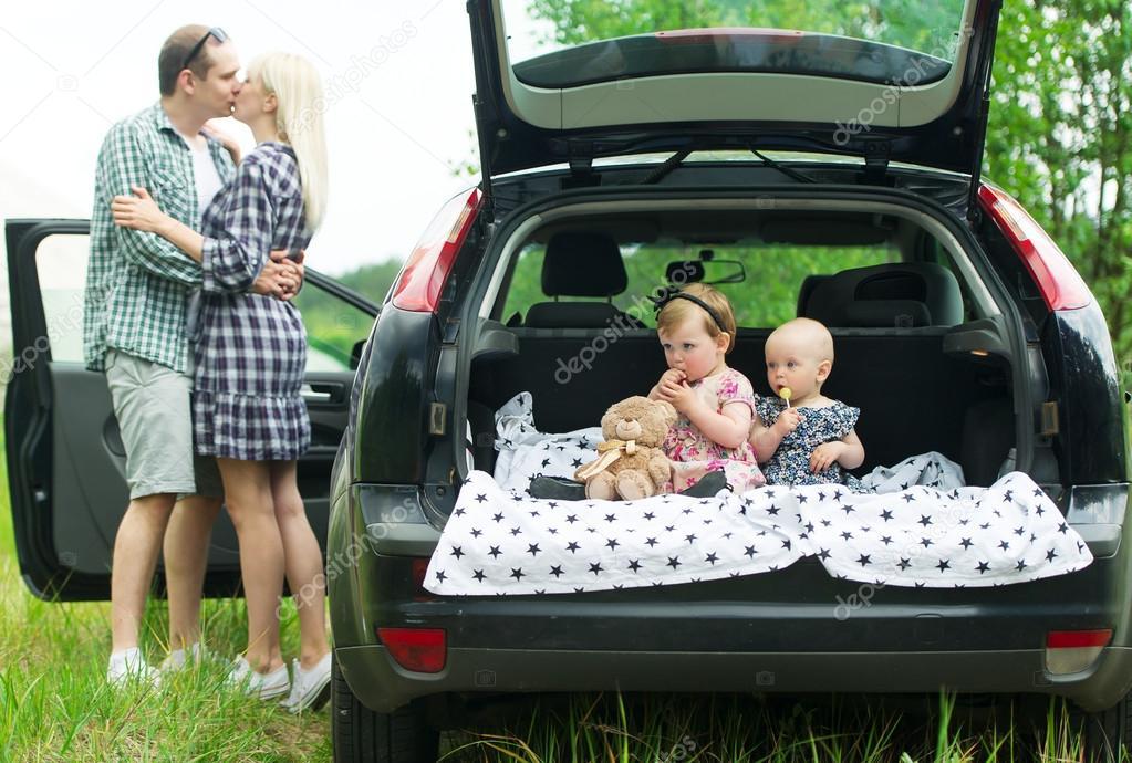 Kinderen zitten in de auto kofferbak ouders staan in de buurt en