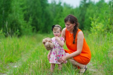 Mother and her little daughter on a green meadow.