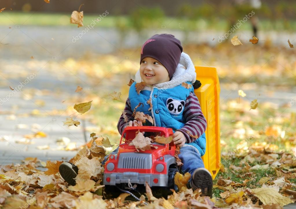The kid plays with a toy machine in autumn park