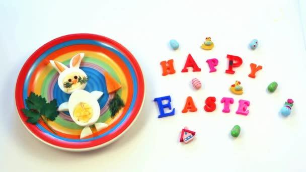 Osterfrühstück für Kinder. Hase aus gekochten Eiern auf buntem Teller, weißer Hintergrund, Aufschrift Frohe Ostern, Draufsicht