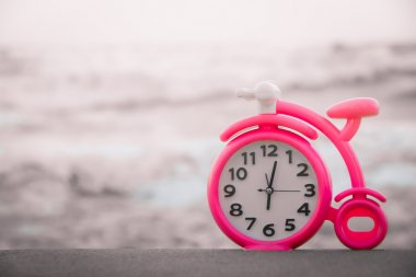 Pink clock on sand