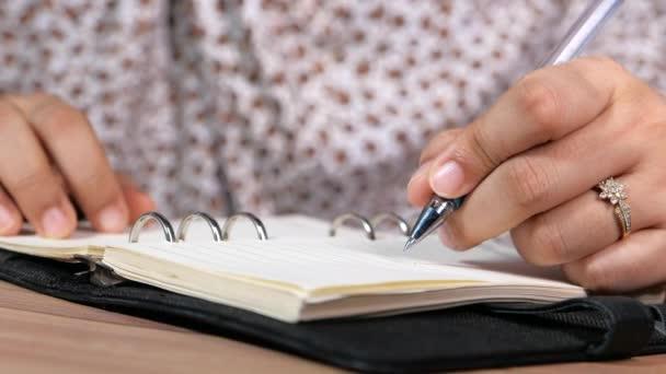 Közelkép a nők kézírásáról jegyzetfüzetben.