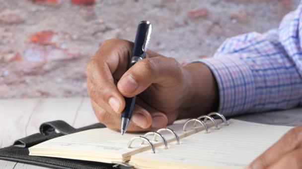 Közelkép férfi kézírás jegyzettömbön.