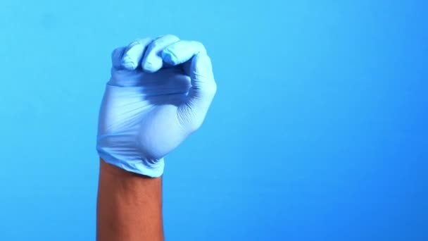 Mann Arzt mit medizinischem Handschuh vor blauem Hintergrund Nahaufnahme