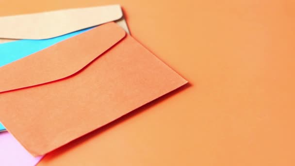 colorful envelope on orange background close up .