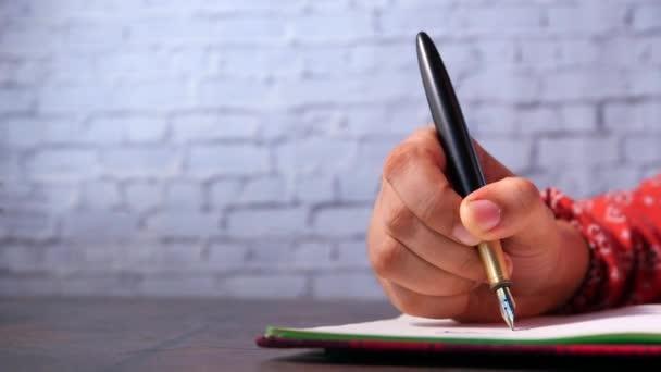Közelkép a női kézírás töltőtollal jegyzettömbön.
