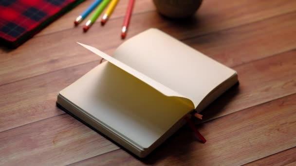 nyitott könyv és egy ceruza a fa asztalon