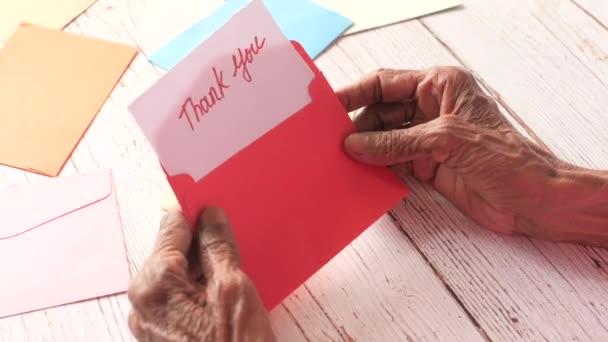Seniorin hält Dankesbrief in der Hand, Rückansicht