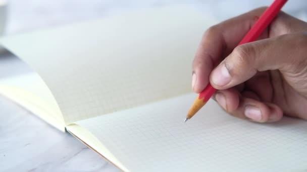 Közelkép férfi kézírás ceruzával jegyzettömbön.
