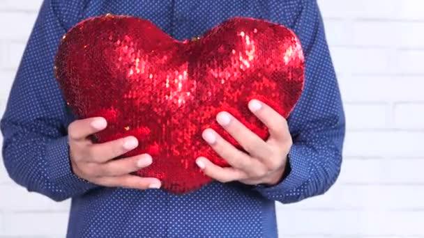 ruka drží červený symbol srdce zblízka