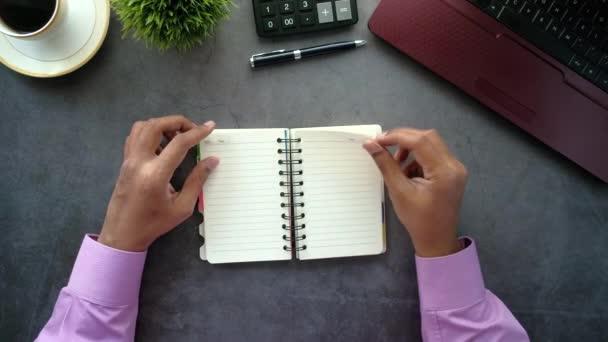 top view of mans kéz fordult egy csipogó egy jegyzettömb laptop az asztalon