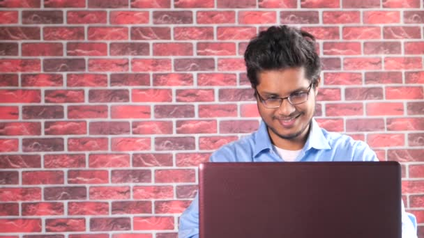 happy young asian man working on laptop with copy space