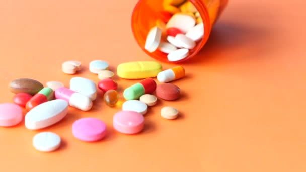 Close up of many colorful pills and capsules on orange background