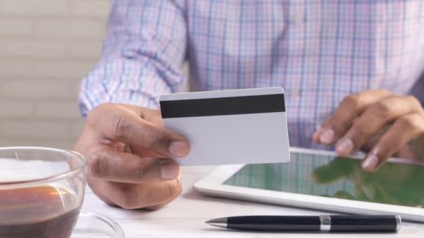 Mann hält Kreditkarte in der Hand und nutzt digitales Tablet