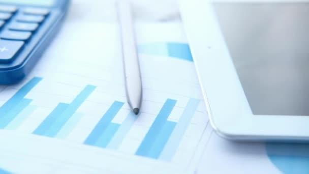 detailní snímek finančního grafu, kalkulačky a digitálního tabletu na stole
