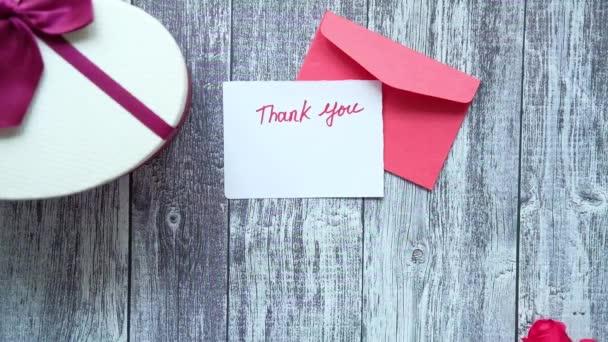 Dankeschön-Nachricht, Umschlag und Rosenblume auf Holztisch