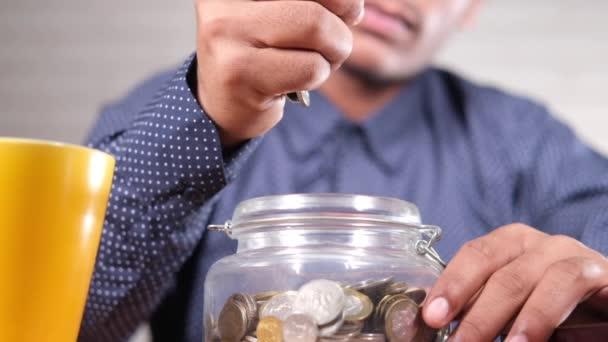 zpomalený pohyb mladého muže shazovat mince do sklenice