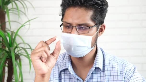 Junger Mann mit chirurgischer Gesichtsmaske hält medizinische Pille in der Hand