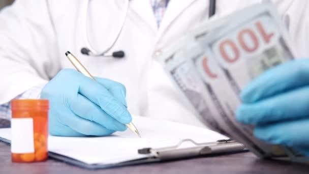 Arzt schreibt Rezept auf Schreibtisch und hält uns Dollar-Bargeld